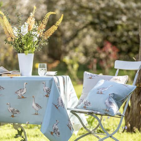 Clarke and Clarke -  Blighty Fabric Collection - A goose print on a pale blue tablecloth, with matching blue and grey cushions on asimple folding chair, with a white vase
