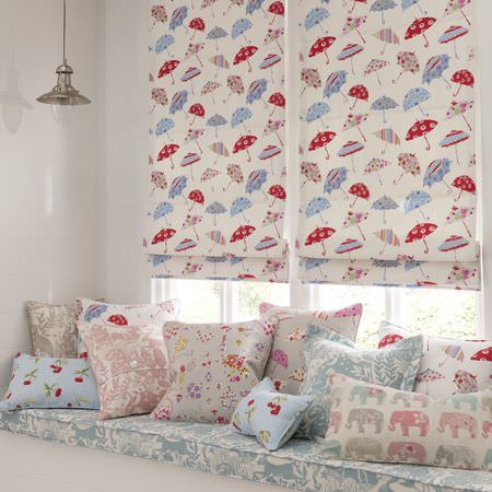 Clarke and Clarke -  Blighty Fabric Collection - Blue, red, pink and cream umbrella, elephant and floral patterns on blinds,a window seat , and various scatter cushions
