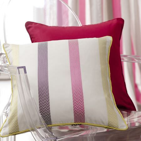 Clarke and Clarke -  Boutique Fabric Collection - A close-up photo of a white cushions with pink and purple herringbone stripes, and a plain pink red cushion on a modern chair