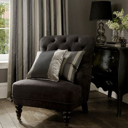 Clarke and Clarke -  Boutique Fabric Collection - A classic black upholstered chair with grey and silver striped cushions, and grey, champagne and white striped curtains, for a classic house