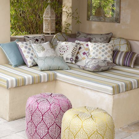 Clarke and Clarke -  Bukhara Fabric Collection - White patterned cushions on a striped corner seat cushion with Moroccan style pouffes