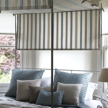 Clarke and Clarke -  Cadoro Fabric Collection - Metal framed bed with pastel striped tie-on canopy, blue and cream scatter cushions, and a lamp with a cream lampshade
