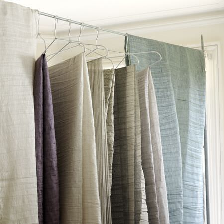Clarke and Clarke -  Cadoro Fabric Collection - Folds of neutral coloured, light blue and purple fabric, hanging from white wire coat hangers
