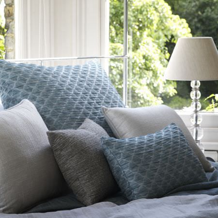 Clarke and Clarke -  Cadoro Fabric Collection - Square blue textured pillow, matching cushion, plain grey, silver and white cushions, and a lamp with a glass ball stand and a cream shade