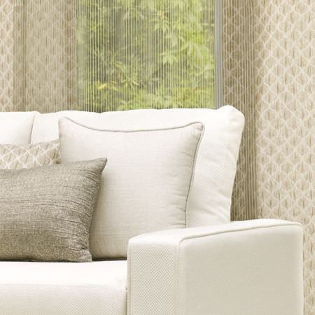Clarke and Clarke -  Cadoro Fabric Collection - Off-white fabric sofa with cream, champagne and pewter coloured scatter cushions, in front of fabric with a cream and champagne pattern