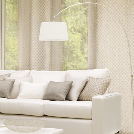 Clarke and Clarke -  Cadoro Fabric Collection - Arched metal floor lamp with large white shade, over a cream sofa with plain and patterned scatter cushions, and matching fabric behind