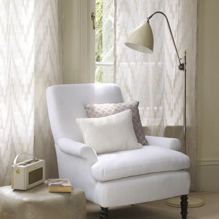 Clarke and Clarke -  Cadoro Fabric Collection - White armchair with two textured white and taupe cushions, cream floor lamp, zigzag curtains, stone coloured cube footstool, vintage radio