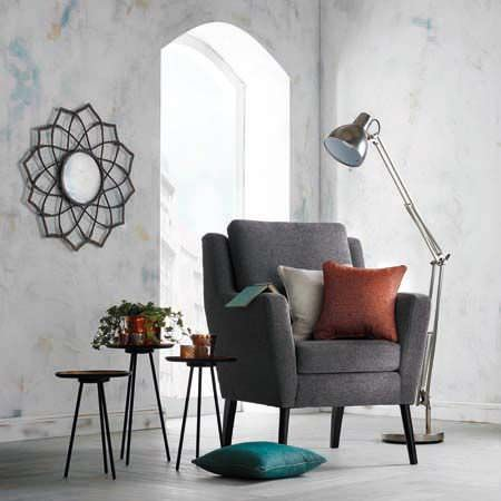 Clarke and Clarke -  Casanova Fabric Collection - A dark grey armchair with three scatter cushions, a grey floor lamp,three round black tables,and a framed round mirror