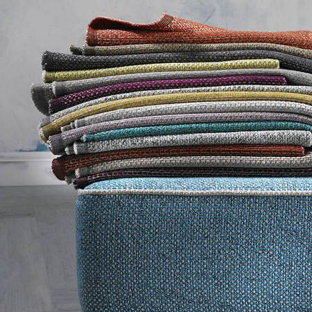 Clarke and Clarke -  Casanova Fabric Collection - Fabrics made in various different plain colours, folded up and stacked on top of a large powder blue coloured seat cushion