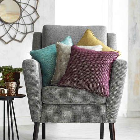 Clarke and Clarke -  Casanova Fabric Collection - Grey armchair with black legs, plain aqua, beige, plum and yellow scatter cushions, 2 round black tables, vases and a mirror
