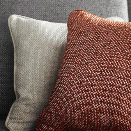 Clarke and Clarke -  Casanova Fabric Collection - A red and white woven cushion with a plain oyster white coloured cushion, on a plain light grey armchair