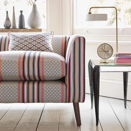 Clarke and Clarke -  Chateau Fabric Collection - Modern upholstered sofa decorated with a vibrant pattern of stripes and diamond-like shapes