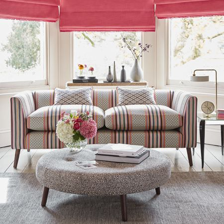 Clarke and Clarke -  Chateau Fabric Collection - Modern Roman blinds in vibrant pink shade, upholstered coffee table and a sofa with a colourful design