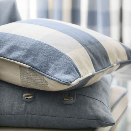 Clarke and Clarke -  Country Linens Fabric Collection - Soft denim blue cushion with button detail, below a cushion with the same blue, cream and grey making up a large checkered pattern