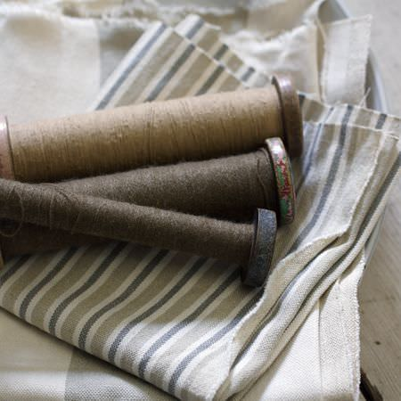 Clarke and Clarke -  Country Linens Fabric Collection - Old fashioned spools of dark brown and beige thread, with two different fabrics with narrow and thin neutrally coloured stripes