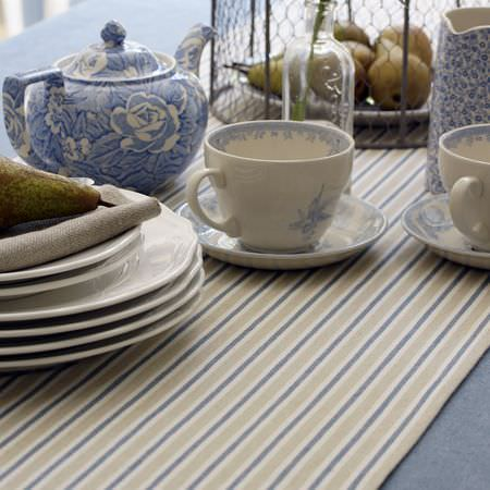 Clarke and Clarke -  Country Linens Fabric Collection - Striped blue, grey and cream table runner, blue tablecloth, white plates, and blue and white floral teacups, saucers, a teapot and milk jug