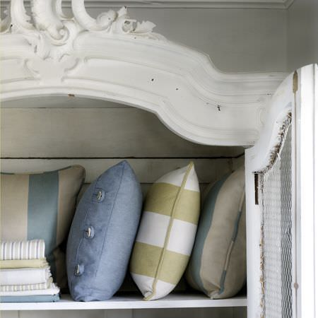 Clarke and Clarke -  Country Linens Fabric Collection - Distressed white wooden cabinet with mesh door, filled with a pile of striped and plain fabrics and cushions in green, white, blue and beige