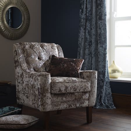 Clarke and Clarke -  Crush Fabric Collection - Textured fabrics covering a silver armchair, dusky blue curtains, brown, silver and blue cushions, with a round mirror