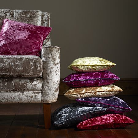 Clarke and Clarke -  Crush Fabric Collection - Grey, purple, gold, magenta and lime cushions beside a silver armchair with a pink cushion, all made from textured fabrics