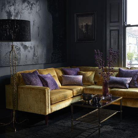 Clarke and Clarke -  Dimensions Fabric Collection - A rich gold corner sofa with purple and gold scatter cushions, a glass and metal coffee table, and a tall black floor lamp