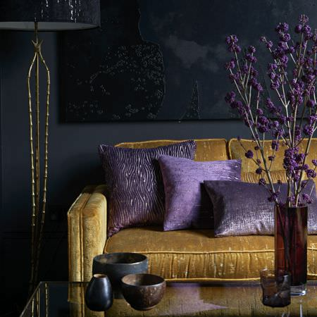 Clarke and Clarke -  Dimensions Fabric Collection - Purple cushions on a rich gold sofa, with a glass table, a large black floor lamp, glass vases, and black and brown pots