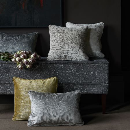 Clarke and Clarke -  Dimensions Fabric Collection - Subtly patterned silver, grey, white and green cushions lying with a bunch of flowers on a dark grey sofa with wood legs