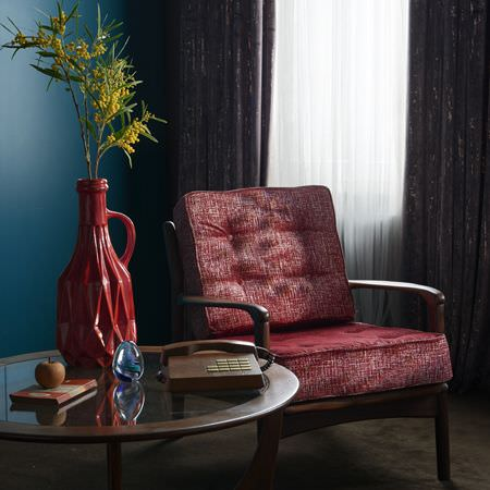 Clarke and Clarke -  Dimensions Fabric Collection - A round wood and glass table, red seat and back cushions to a wood framed armchair, a red vase and a brown vintage telephone