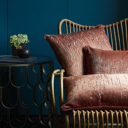 Clarke and Clarke -  Dimensions Fabric Collection - Three subtly patterned, slightly shiny light red cushions on a chair made from woven canes, beside a round mesh table
