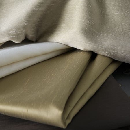 Clarke and Clarke -  Emperor Fabric Collection - Folds of cream, gold and champagne coloured silk effect fabrics