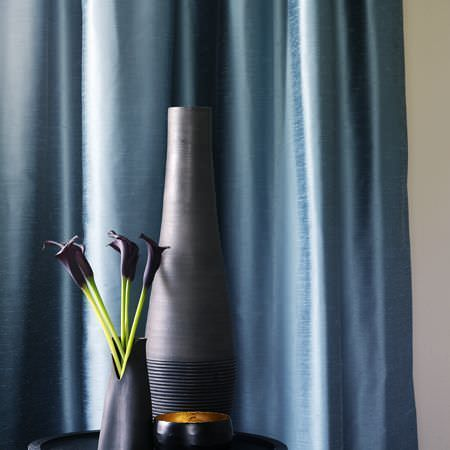 Clarke and Clarke -  Emperor Fabric Collection - Blue silk effect curtains, with round table, blue vase with horizontally striped base, blue vase with cut-out