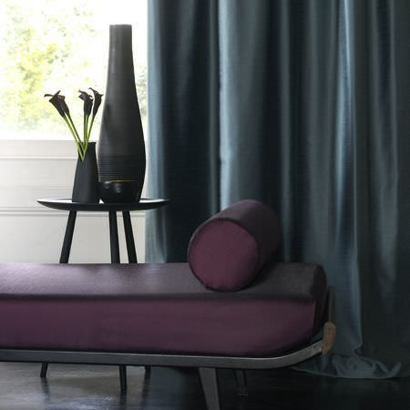 Clarke and Clarke -  Emperor Fabric Collection - Black metal framed chaise longue with deep purple seat and bolster cushions, dark teal curtains, small black table with black pot and vases