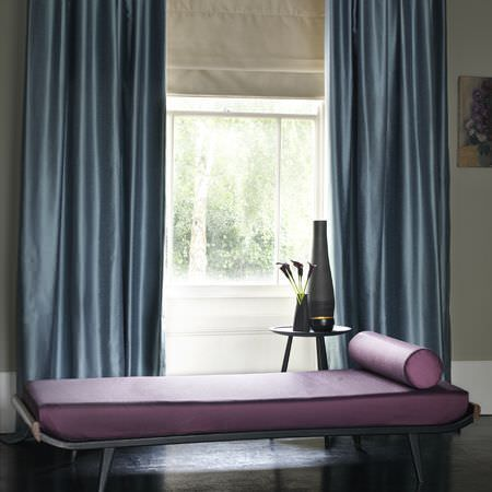 Clarke and Clarke -  Emperor Fabric Collection - Dusky blue silk effect curtains, a metal chaise longue with purple cushions, a round table, two different sized black vases and a black pot