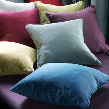 Clarke and Clarke -  Emperor Fabric Collection - A purple seat with seven plain scatter cushions in white, cherry red, green, purple, yellow, light blue and bright blue