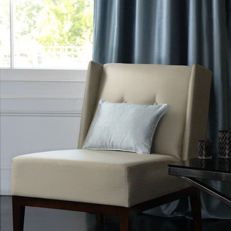 Clarke and Clarke -  Emperor Fabric Collection - Square padded chair in cream leatherette with wooden legs, a silver cushion, plain blue silk effect curtains, a black table with black cups