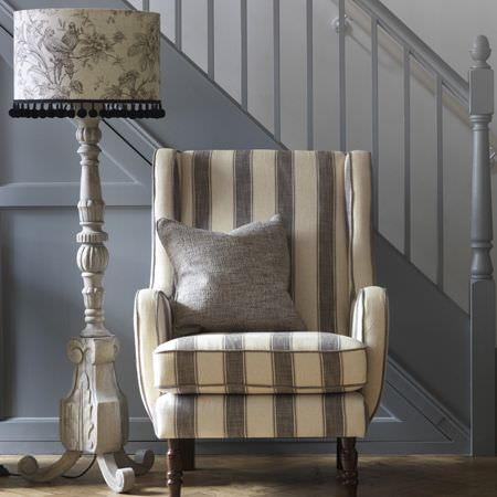 Clarke and Clarke -  Fairmont Fabric Collection - Armchair with wide cream and grey stripes, plain grey scatter cushion, floor lamp with a large grey carved stand and a floral, fringed shade