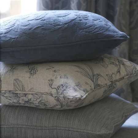 Clarke and Clarke -  Fairmont Fabric Collection - Cushion in a solid shade of blue with a textured floral design, grey cushion with blue floral line drawings, and subtly striped blue cushion