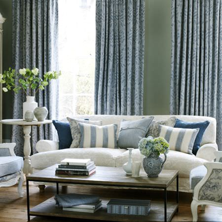 Clarke and Clarke -  Fairmont Fabric Collection - Cream sofa, cushions in different shades of blue - striped, plain and patterned, wooden coffee table, patterned curtains, vases, side table