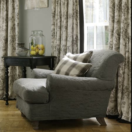 Clarke and Clarke -  Fairmont Fabric Collection - Large-seated padded grey armchair with grey and white checked cushions, grey and white floral curtains, black side table, vase and glass jar