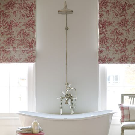 Clarke and Clarke -  Fairmont Fabric Collection - White bath with side taps and high vintage over-bath shower head, red and white floral blinds, and matching checked cushion on a white chair
