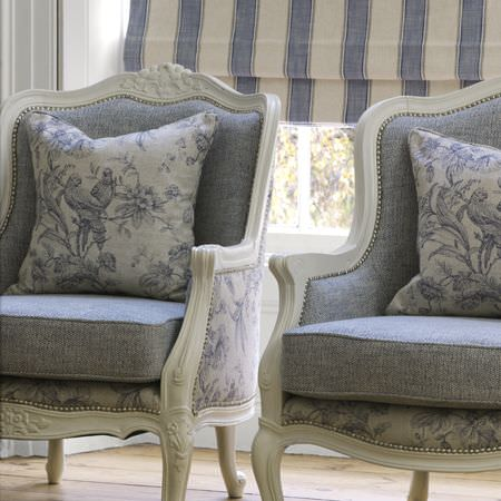 Clarke and Clarke -  Fairmont Fabric Collection - Carved white armchairs with blue and white floral fabric outers (and matching cushions), plain blue inners and seat cushions, striped blinds