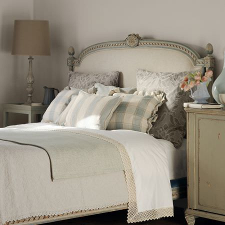 Clarke and Clarke -  Fairmont Fabric Collection - Bed with cream and green headboard, plain grey and cream lace-edged bedding, patterned cushions, wooden tables, a beige lamp, and vases