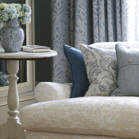 Clarke and Clarke -  Fairmont Fabric Collection - White sofa with subtle cream textured floral design, plain blue and floral cushions, blue patterned curtains, round cream table, and vase
