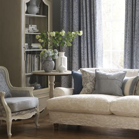 Clarke and Clarke -  Fairmont Fabric Collection - White and cream sofa, blue and white armchair, blue and white cushions, blue curtains, round white occasional table, white or floral vases