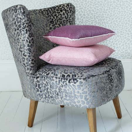 Clarke and Clarke -  Floribunda Fabric Collection - A chunky, retro chair upholstered in textured leopard skin fabric in a clean white room with pink cushions