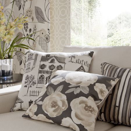 Clarke and Clarke -  Folia Fabric Collection - Grey cushion with cream florals, grey and cream striped cushion, cream cushion with grey house prints, coordinating curtains and cream sofa
