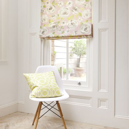 Clarke and Clarke -  Folia Fabric Collection - Plain white chair with wooden legs, with a pale green cushion with white circles printed on it, and a pink, green and cream floral blind
