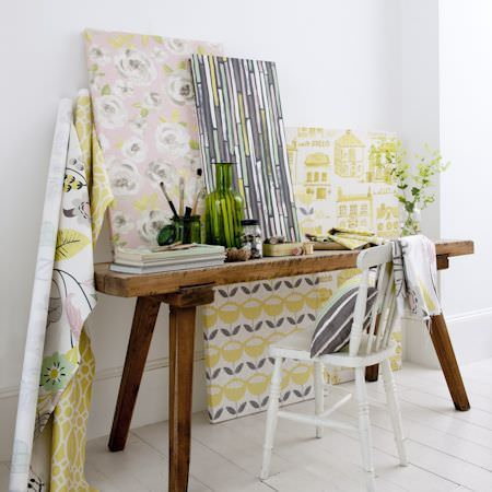Clarke and Clarke -  Folia Fabric Collection - Rustic wooden bench with white wood chair, patterned and striped fabrics in greens, greys, creams and pinks, a cushion and a green vase