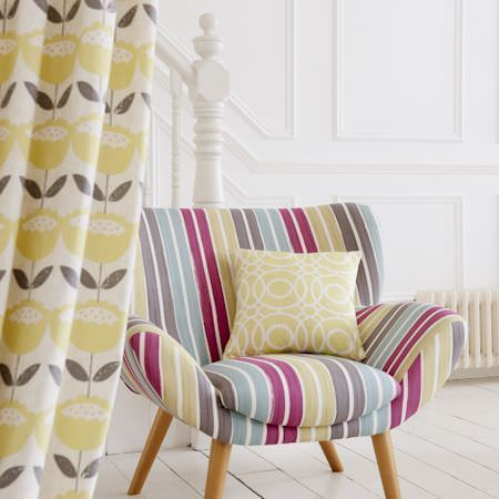 Clarke and Clarke -  Folia Fabric Collection - Armchair with stripes of pink, green, grey, blue and cream, a cushion with a green and white circle print, and green and cream floral fabric