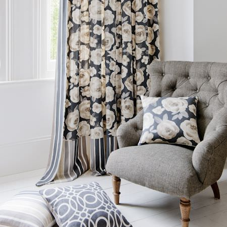 Clarke and Clarke -  Folia Fabric Collection - Grey padded armchair  with floral cushion and matching fabric, a grey and cream striped cushion and curtains, and a patterned cushion