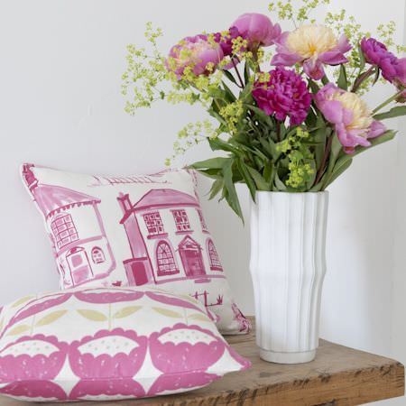 Clarke and Clarke -  Folia Fabric Collection - White ribbed vase with a pink and white house print cushion and a white cushion with a repeated pink and green stylised flower design